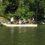 W oddali grupa turystów płynie z flisakiem po dunajcu