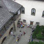 Widok na dziedziniec grupa zwiedzających z przewodnikiem