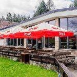 restauracja Flis przystan flisacka z zewnatrz ławeczki i parasole